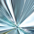 Perspective wide angle view of modern light blue illuminated and spacious high-speed moving commercial escalator with fast blurred trail of handrail in vanishing traffic motion in airport corridor — Stock Photo #26755483