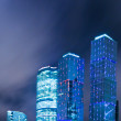 Panoramic and perspective wide angle view to steel blue background of glass high rise building skyscrapers in modern futuristic downtown at night Business concept of successful industrial architecture — Stock Photo #26755619