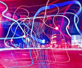 Colorful ribbons over night streets — Stock fotografie