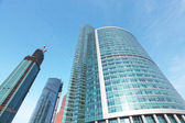Panoramic and prospective wide angle view to steel light blue background of glass high rise building skyscraper commercial modern city of future. Business concept of successful industrial architecture — Photo