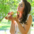 Beautiful young girl with apples in summer park enjoying — Stock Photo #6949793