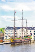 View of a rebuilt Indiaman ship and the Maritime museum in the Amsterdam Harbour — Stockfoto