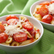 Pasta with tomatoes and salami - Stock Photo