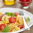 Tortellini with cheese and tomatoes - Stock Photo