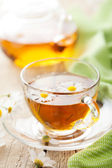 Cup of herbal tea with camomile flowers — Stock Photo