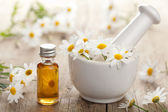 Essential oil and camomile flowers in mortar — Foto Stock