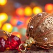 Golden christmas ball over blurred colorful background — Stock Photo