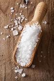 Sea salt in wooden scoop — Stock Photo