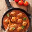 Meatballs with tomato sauce in black pan — Stock Photo