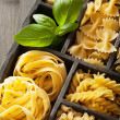 Various pasta in black wooden box — Stock Photo #35177483