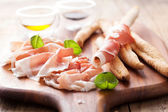 Italian prosciutto ham grissini bread sticks olive oil — Stock Photo