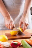Chef hands cutting lemon in kitchen — 图库照片