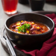 Stock Photo: Mexicchili con carne in black bowl with tortilla