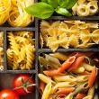 Various pasta in black wooden box — Stock Photo