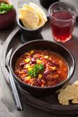 Mexican chili con carne in black bowl with tortilla — Stock Photo