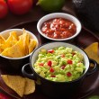 Guacamole with avocado, lime, chili and tortilla chips, salsa — Stock Photo #41211447