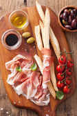 Italian prosciutto ham grissini bread sticks tomato olive oil — Stock Photo