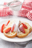 Dusting powder sugar over french toast with strawberry — Stock Photo