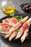 Prosciutto ham and grissini bread sticks. italian antipasto — Stock Photo