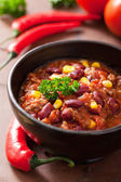 Mexican chili con carne in black plate with ingredients — Stock Photo