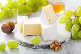 Camembert cheese with grapes, honey and nuts on wooden backgroun — Foto Stock