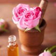 Mortar with rose flowers and essential oil for aromatherapy and — Stock Photo #46252489