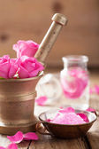 Mortar with rose flowers for aromatherapy and spa  — Stock Photo