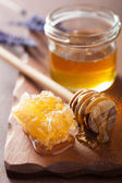 Honeycomb dipper and glass jar on wooden background — Stockfoto