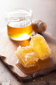 Honeycomb dipper and glass jar on wooden background — Stock Photo