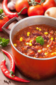 Mexican chili con carne in red rustic pot with ingredients — Stock Photo