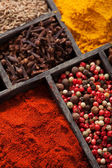 Spices in box pink and black pepper, ground paprika, curry, anis — Stock Photo