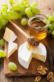 Camembert cheese with grapes, honey and nuts on wooden backgroun — ストック写真