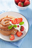 Sweet cinnamon roll with cream and strawberry for breakfast — Stock Photo