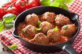 Meatballs with tomato sauce in black pan — ストック写真