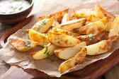 Baked potato wedges with yogurt dip — Stock Photo