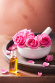 Mortar with rose flowers and essential oil for aromatherapy and  — Stock Photo