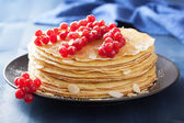 Stack of pancakes with redcurrant and powder sugar  — Stock Photo