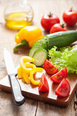 Chopping fresh vegetables cucumber tomatoes pepper and salad lea — Stock Photo