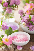 Spa with pink herbal salt and wild rose flowers clover — Stock Photo