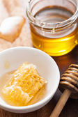 Honeycomb dipper and honey in jar on wooden background — Photo