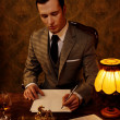 Retro man in grey suit holding a pen — Stock Photo #12454700