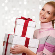 Smiling woman in cashmere sweater with gift boxes — Stock Photo