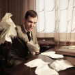 Angry businessman rumples a documents - Stock Photo