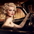 Stock Photo: Woman in retro car against night city.