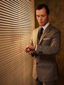 レトロな実業家彼の腕時計を見て — ストック写真
