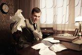 Angry businessman rumples a documents — Stock Photo