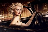 Woman in retro car against night city. — Stock Photo