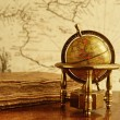 Globe and vintage book against map on a wall. - Photo