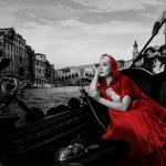 Beautifiul woman in red cloak riding on gandola — Stock Photo