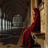 Žena v rudý plášť se modlí sám — Stock fotografie
